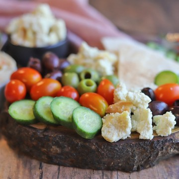 Almond cheese on board with cucumbers, tomatoes, and olives.