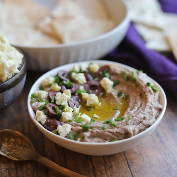 Bowl of olive hummus by non-dairy feta and pita.