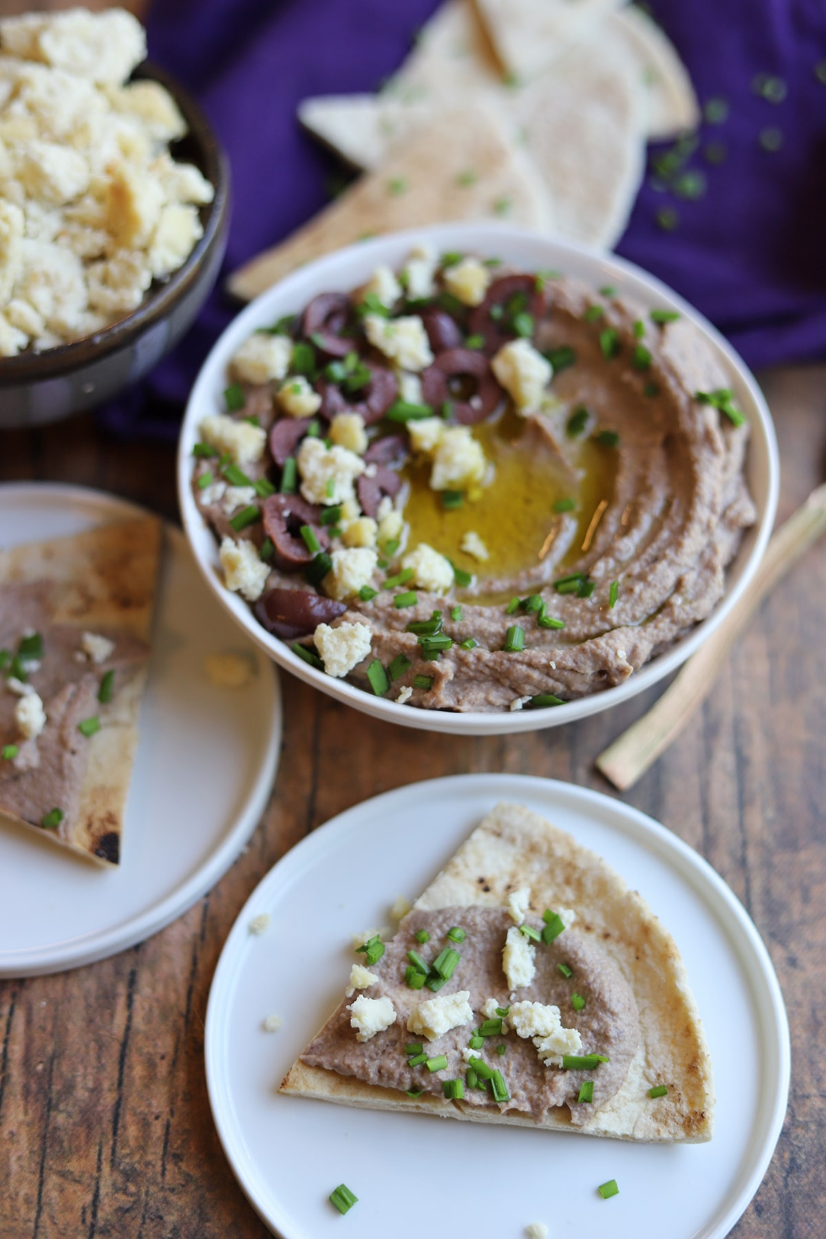 Plate with pita by bowl of hummus.