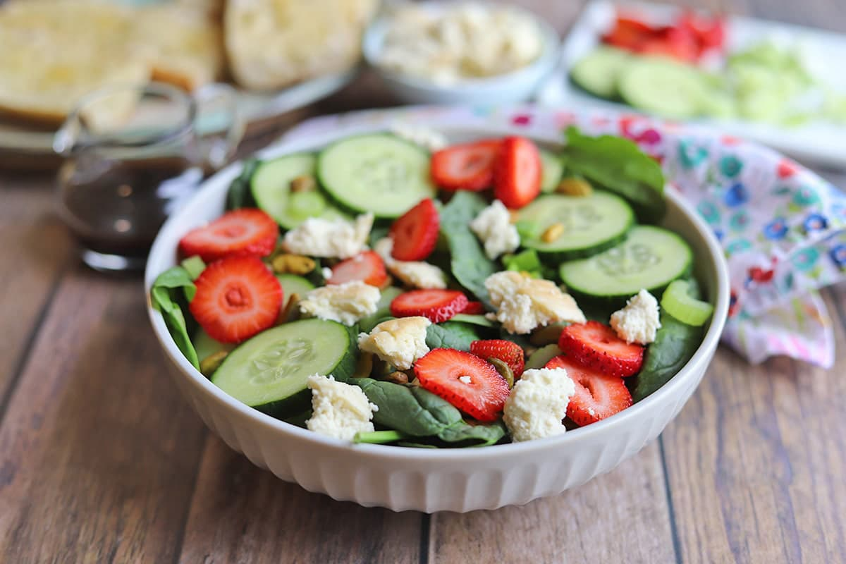 Bowl of salad with strawberries and vegan feta.