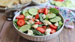 Spinach salad with strawberries, cucumbers, and non-dairy feta.