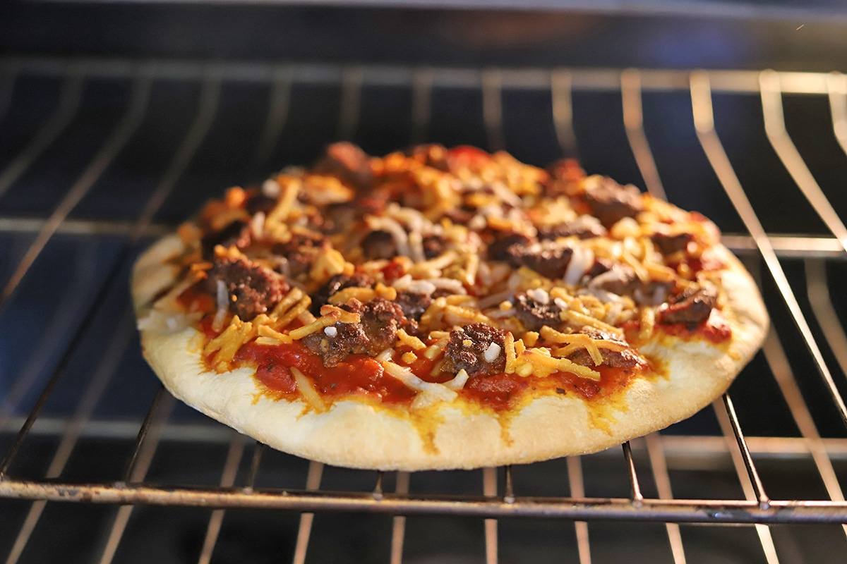 Cheeseburger pizza in oven on grate.