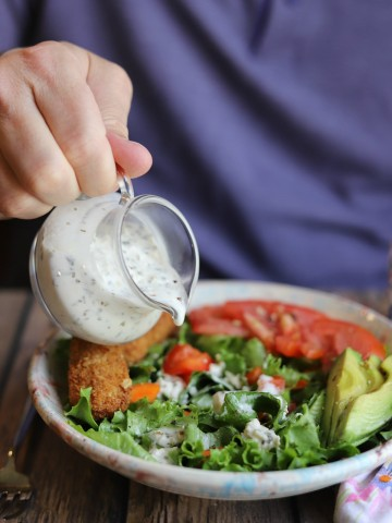 Tiny pitcher with dressing being poured onto salad.