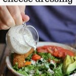 Text overlay: Vegan blue cheese dressing. Dressing being poured from pitcher onto salad.