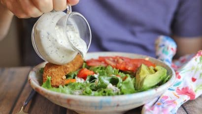 Vegan blue cheese dressing being poured onto salad.