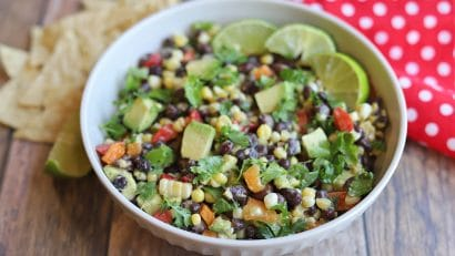 Bowl of black bean corn avocado salad with tortilla chips and red napkin.