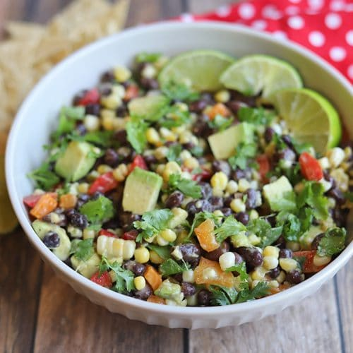 Bowl of black bean corn avocado salad with tortilla chips and red napkin.