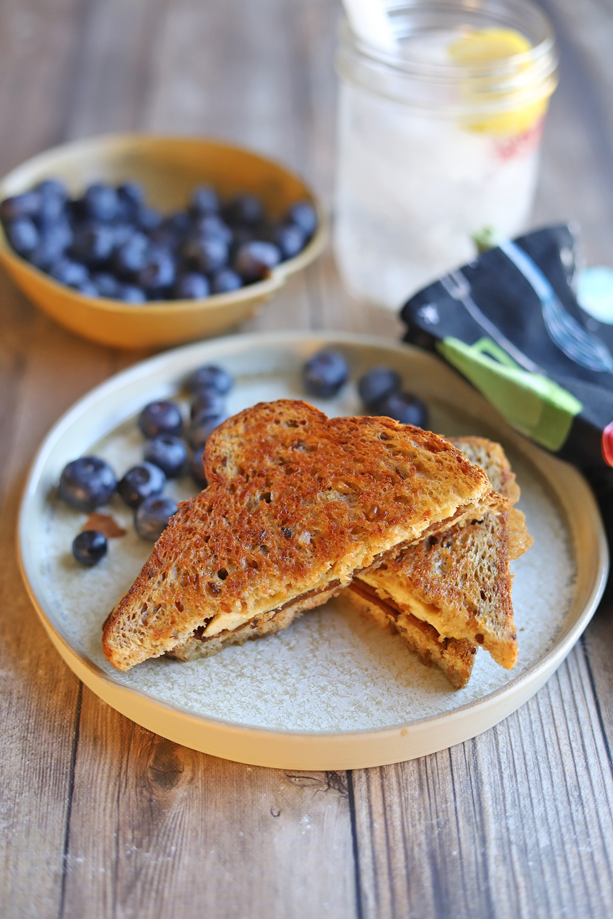 Toasted sandwich on plate with blueberries.