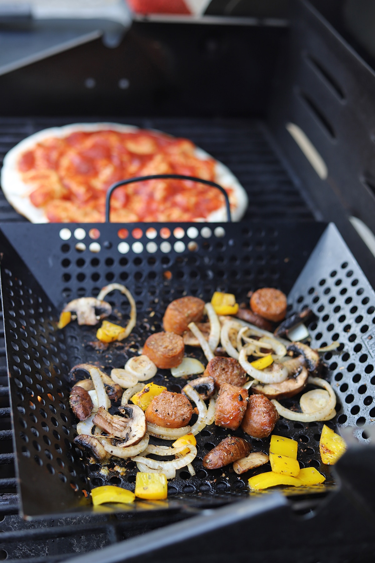 Grill basket with vegetables and pizza crust in background.