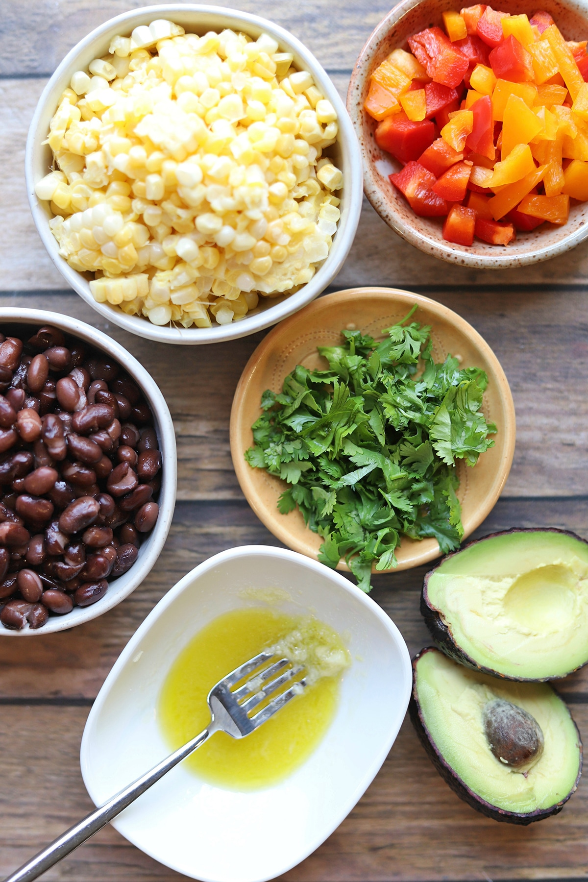 Overhead salad ingredients: avocado, lime dressing, bell pepper, black beans, and corn.