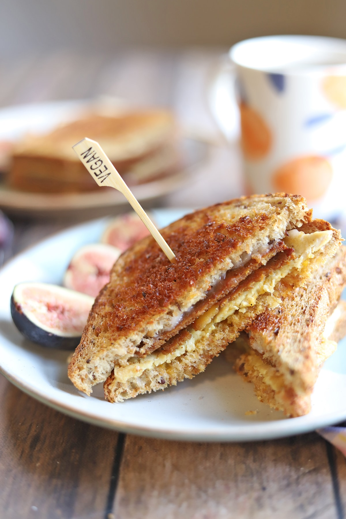Toasted sandwich on plate with figs.