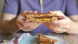 Hands holding breakfast sandwich.