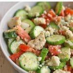 Text overlay: Tomato cucumber salad with vegan feta. Bowl of salad.