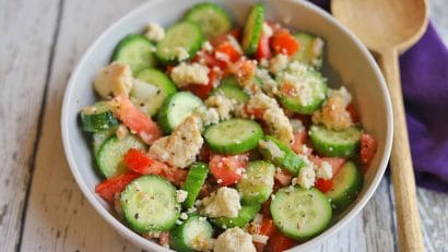 Cucumber tomato salad in bowl by wooden spoon.