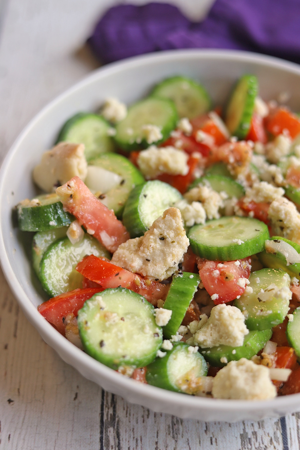Tomato cucumber salad in bowl with vegan feta crumbles.