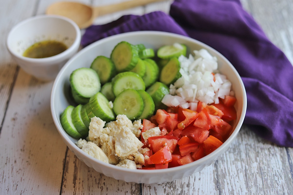 Sliced cucumber, tomatoes, onions, and vegan feta in bowl.