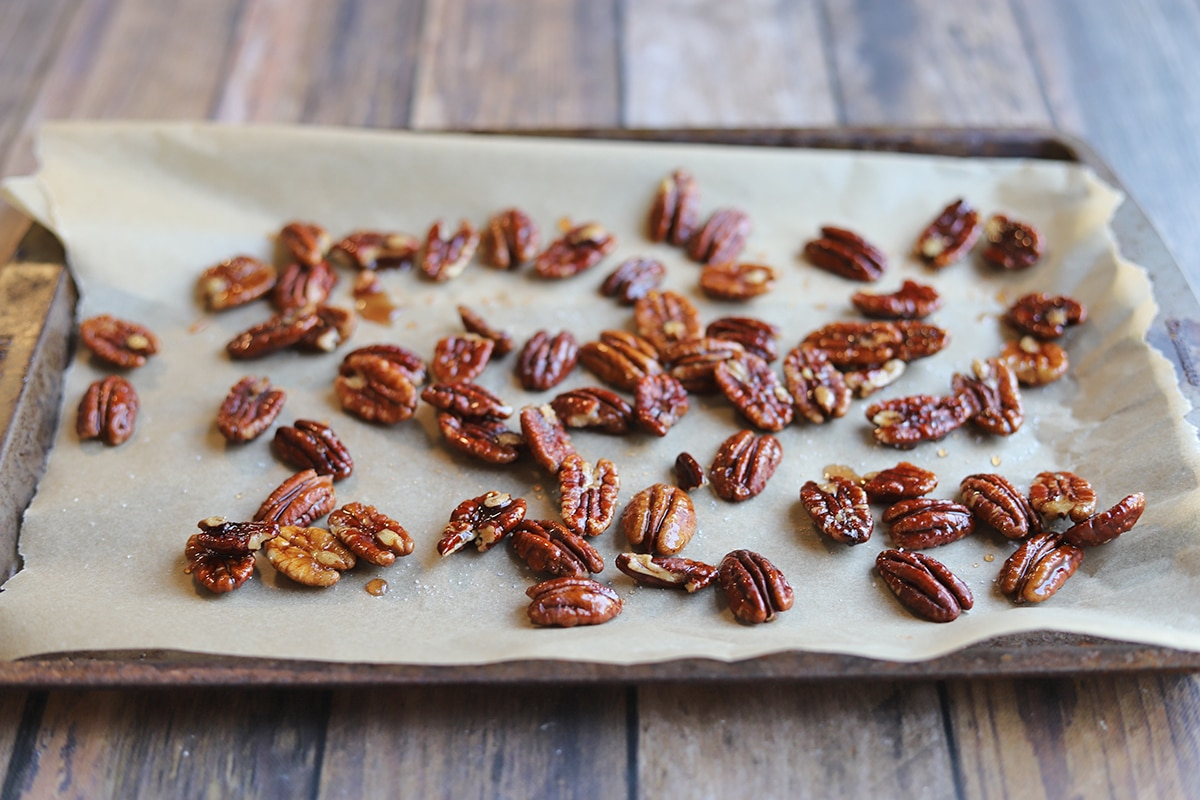 Glazed pecans on parchment paper covered baking sheet.