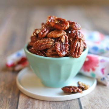Candied pecans in blue bowl on table.