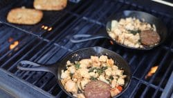 Cast iron skillets on an outdoor grill with tofu scramble and veggie sausage.
