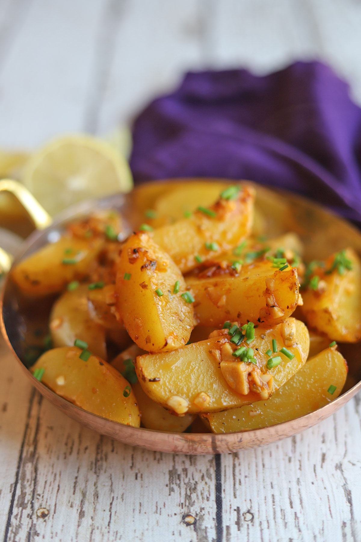 Lemony potatoes garnished with chives in serving dish.
