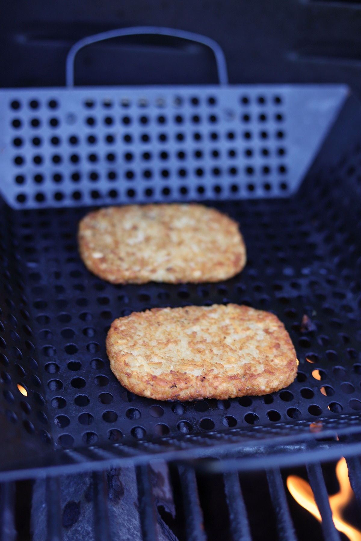 Hashbrowns in a grill basket on the grill.