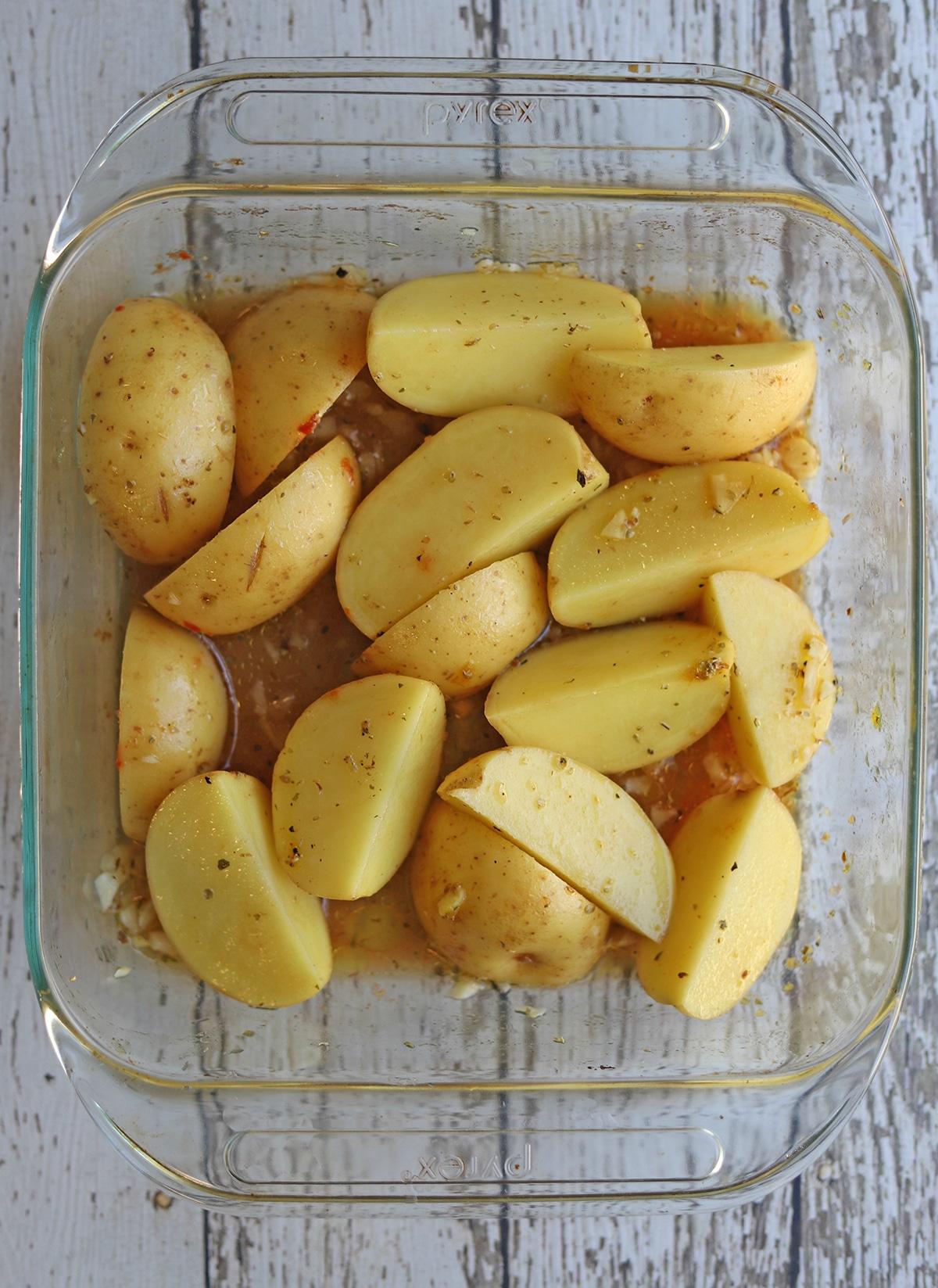 Potatoes in baking dish with seasoned broth.