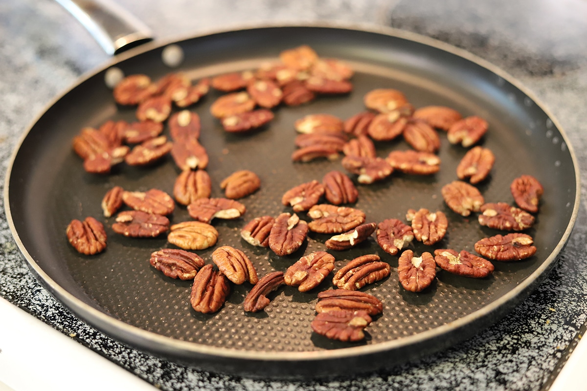 Pecans toasting in skillet on stovetop.