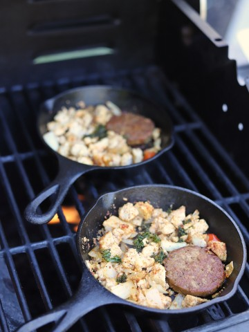 Cast iron breakfast skillets cooking on outdoor grill.