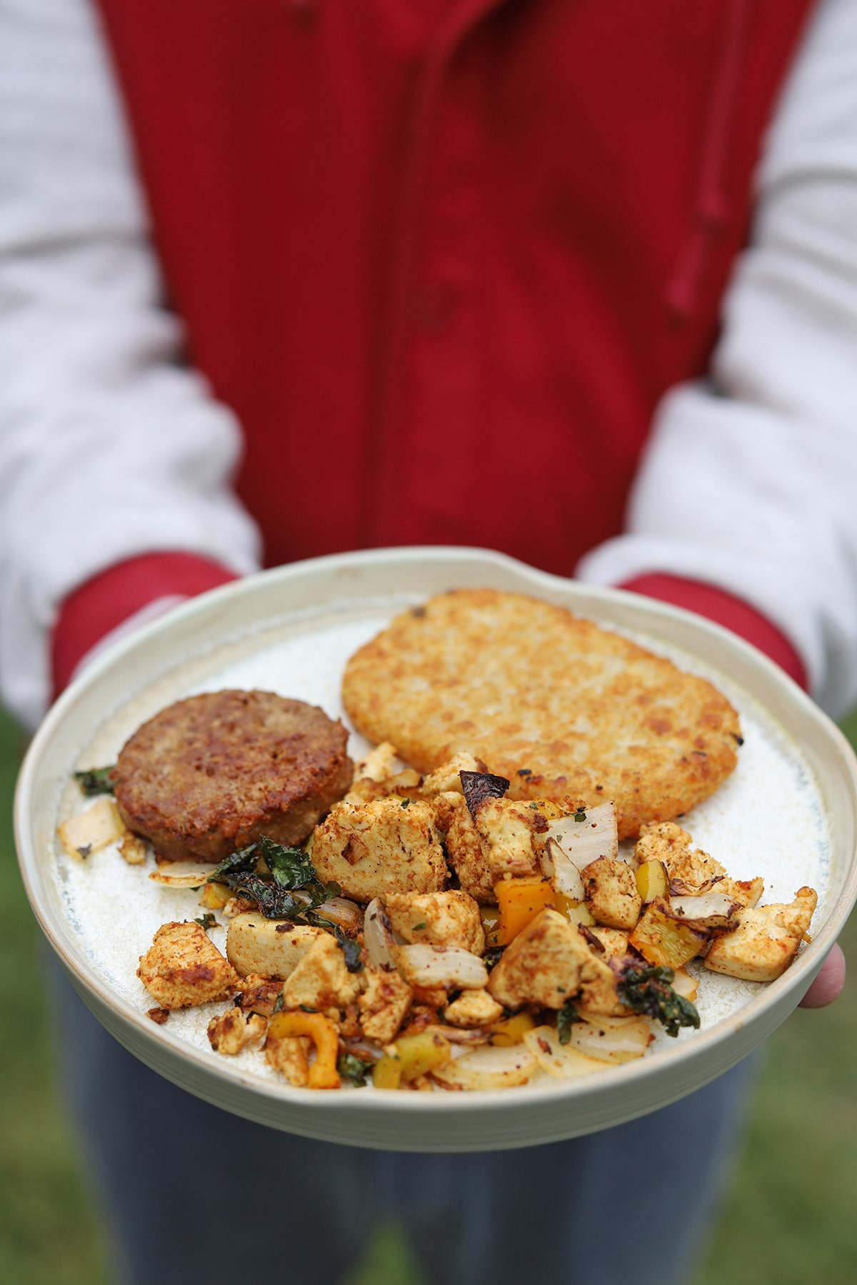 Hands holding plate with tofu scramble, hashbrown patty, and breakfast sausage.