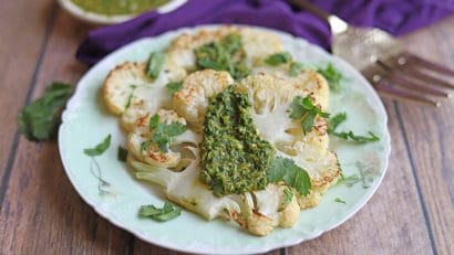 Two slabs of cauliflower on plate with cilantro chimichurri.