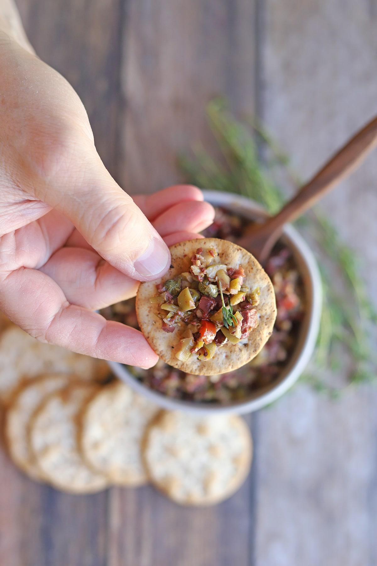 Tapenade on cracker over bowl.
