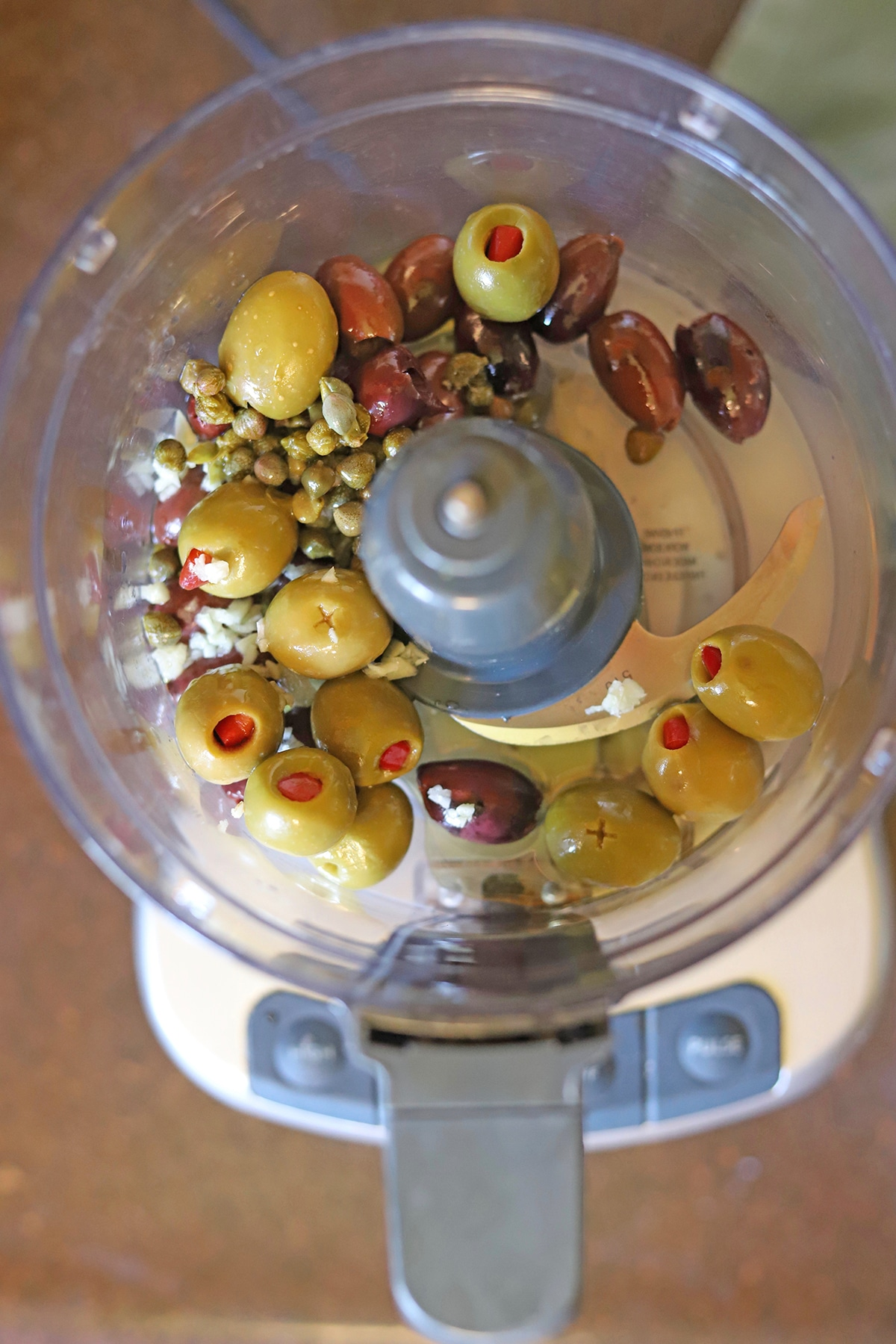 Olives in food processor with capers and garlic.