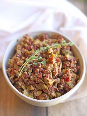 Bowl of chunky olive tapenade in bowl with fresh thyme.