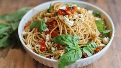Bowl of pasta with basil, roasted tomatoes, and almond feta.