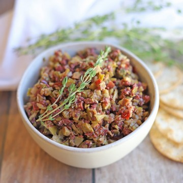 Bowl of olive tapenade with fresh thyme.