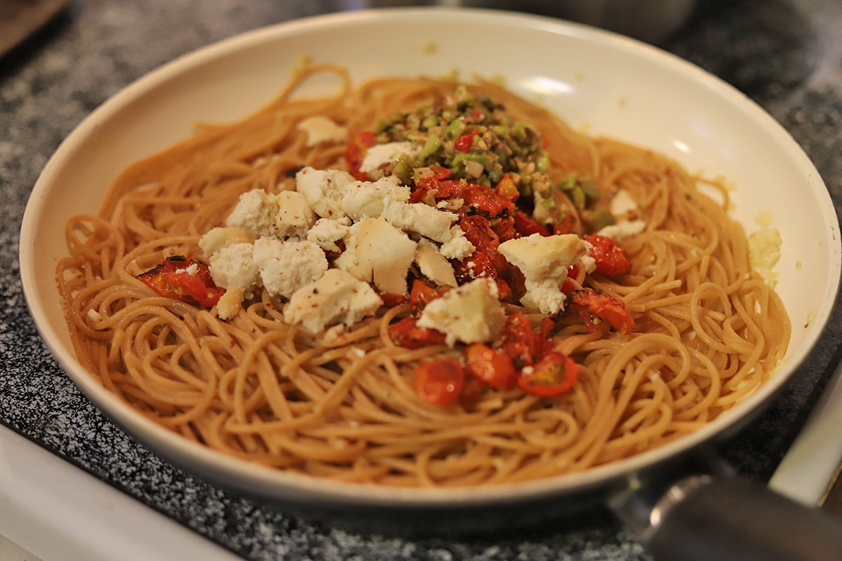 Spaghetti in skillet with olive tapenade, roasted tomatoes, and vegan feta.