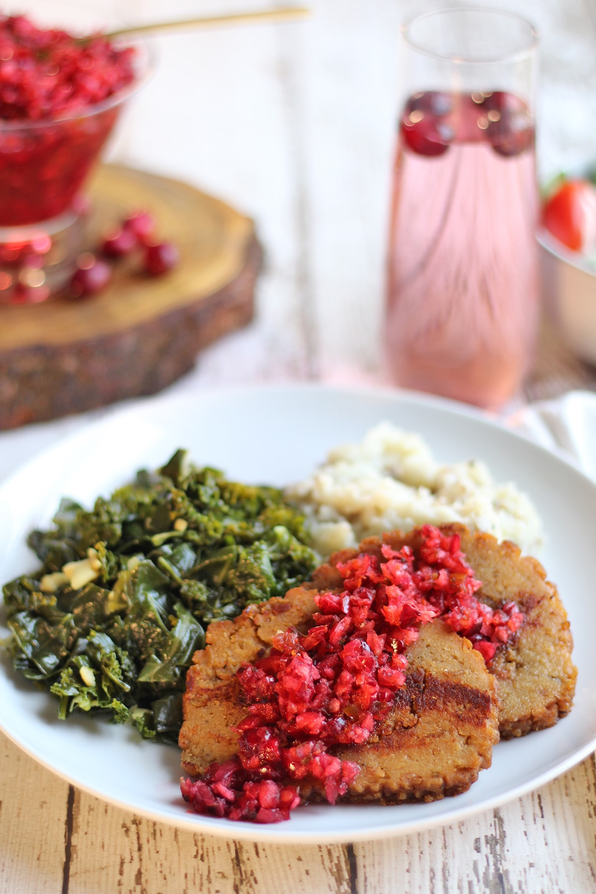 Celebration Roast slices on plate with collard greens, mashed potatoes, and cranberry salsa.