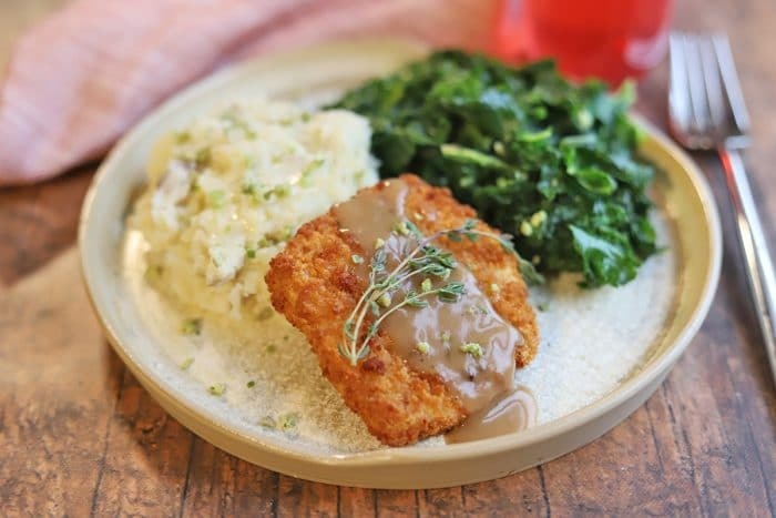 Gardein turk'y cutlet with gravy, mashed potatoes, and greens on plate.