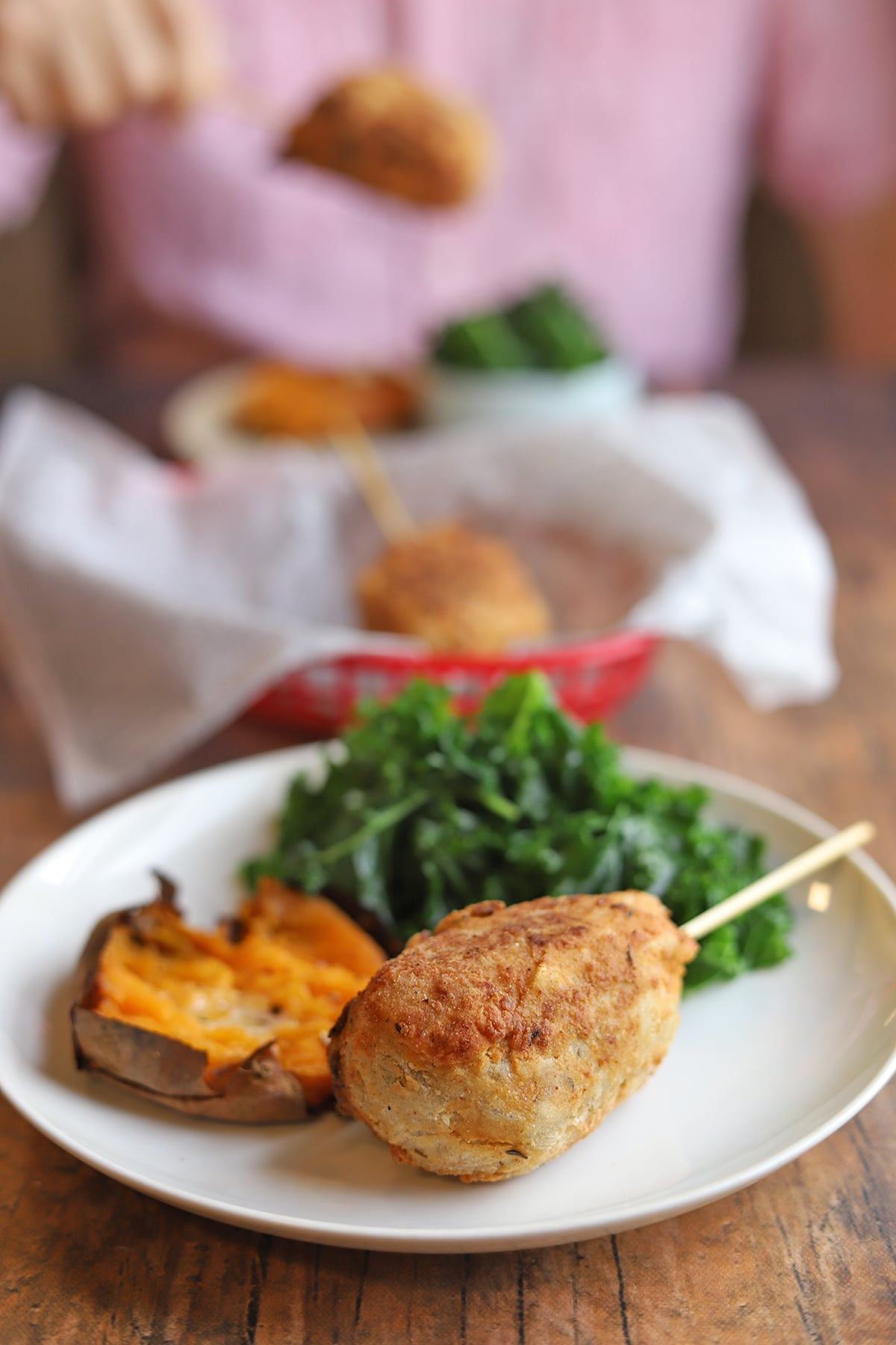 Vegan drumstick on plate with sweet potato and kale.