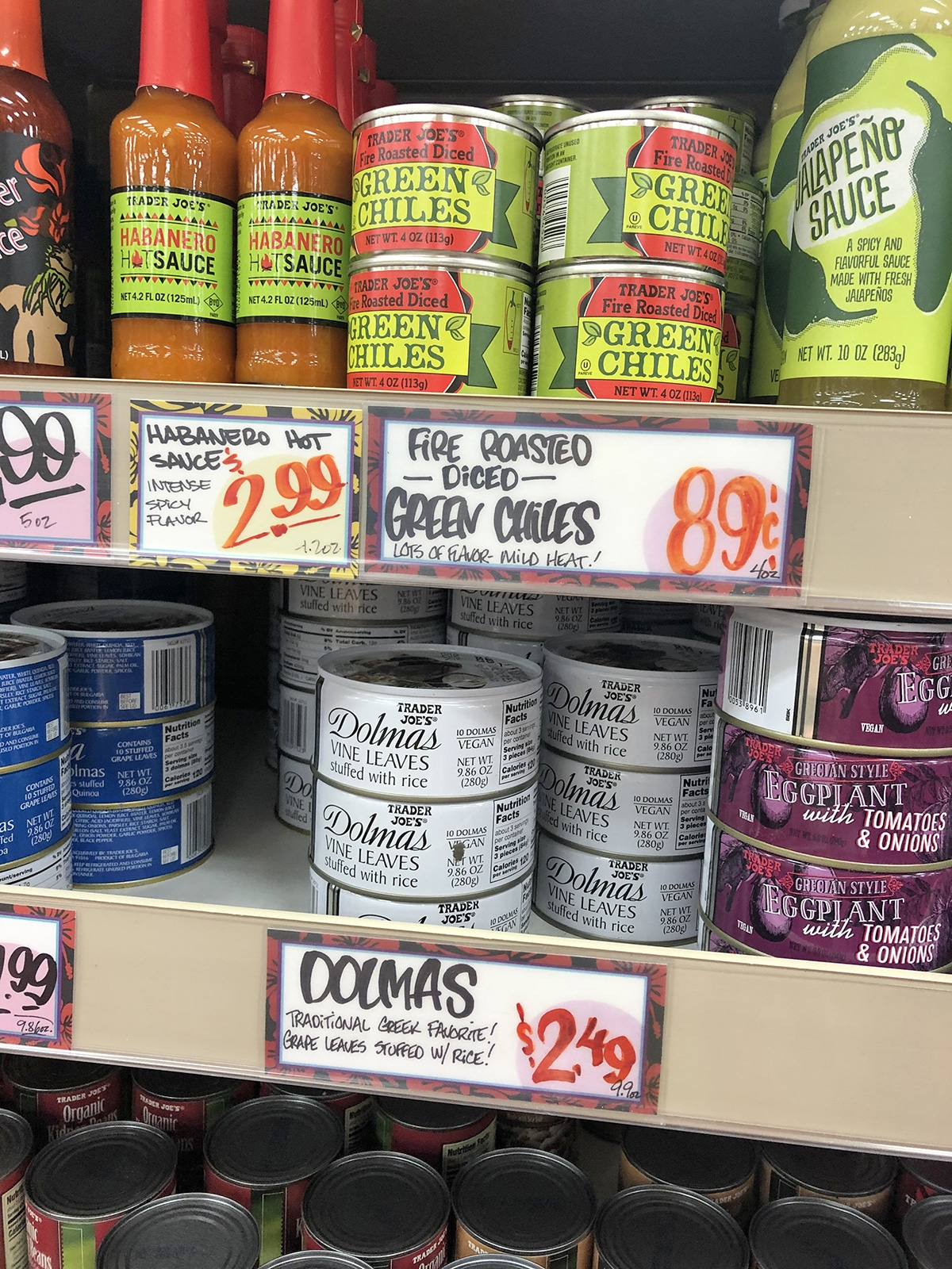 Store shelf at Trader Joe's with dolmas, chilies, and hot sauce.