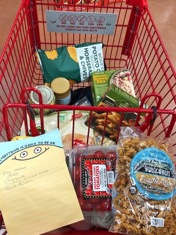 Grocery cart with pasta, tomatoes, and chips.