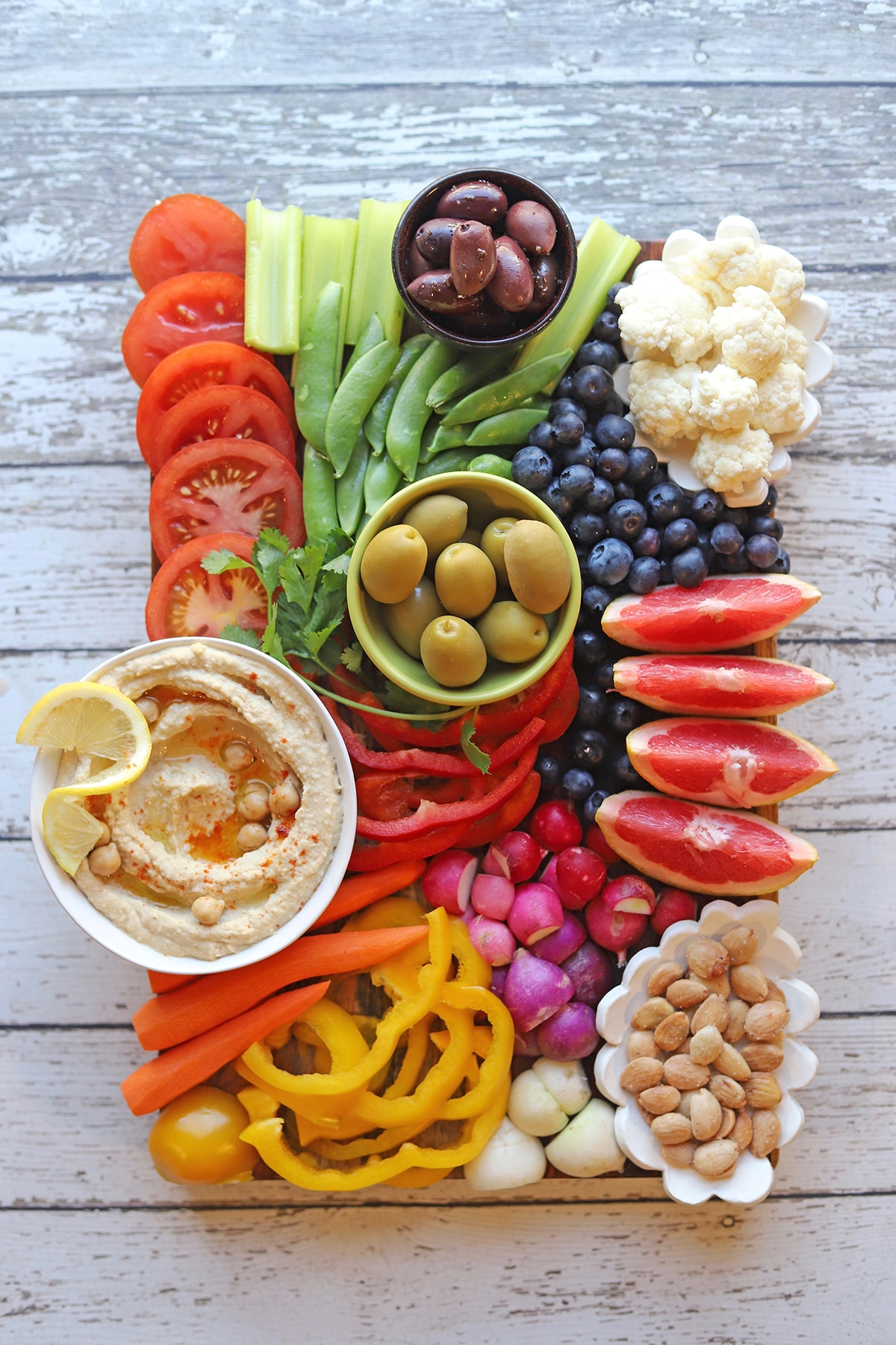 Veggie and fruit platter on table with hummus.