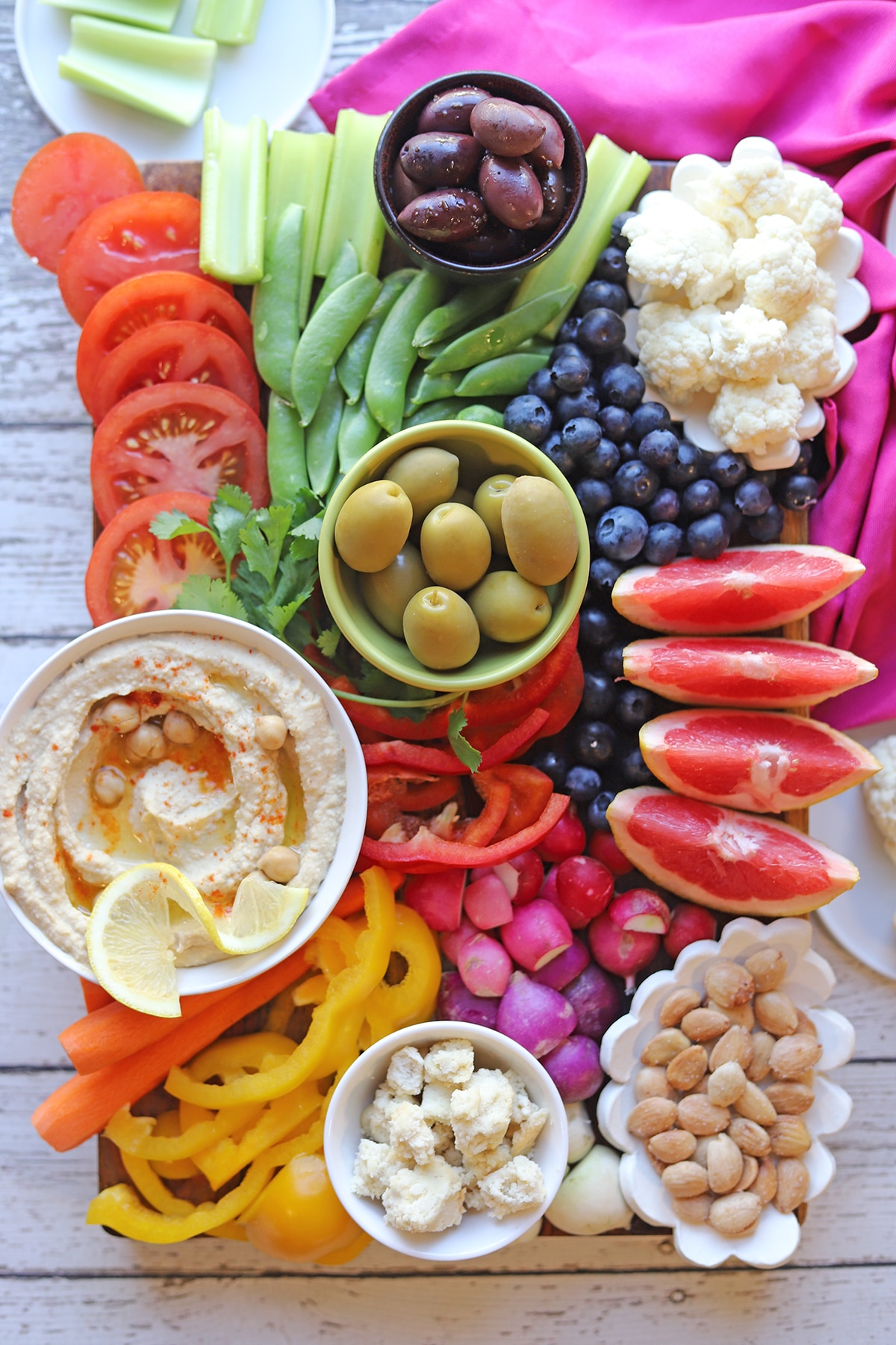 Hummus, olives, vegan feta cheese, and cauliflower on board with vegetables and fruit.