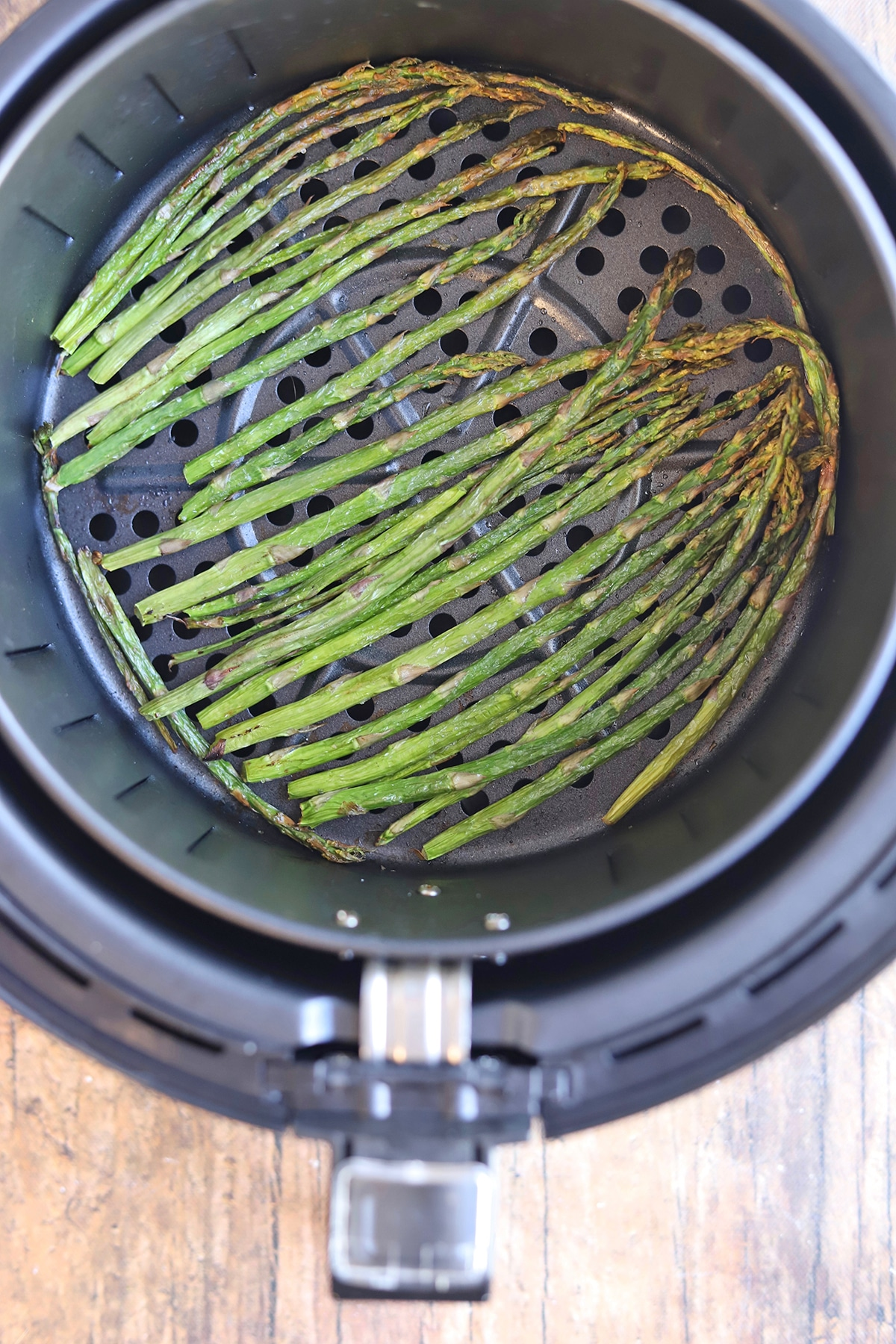 Cooked asparagus in air fryer basket.