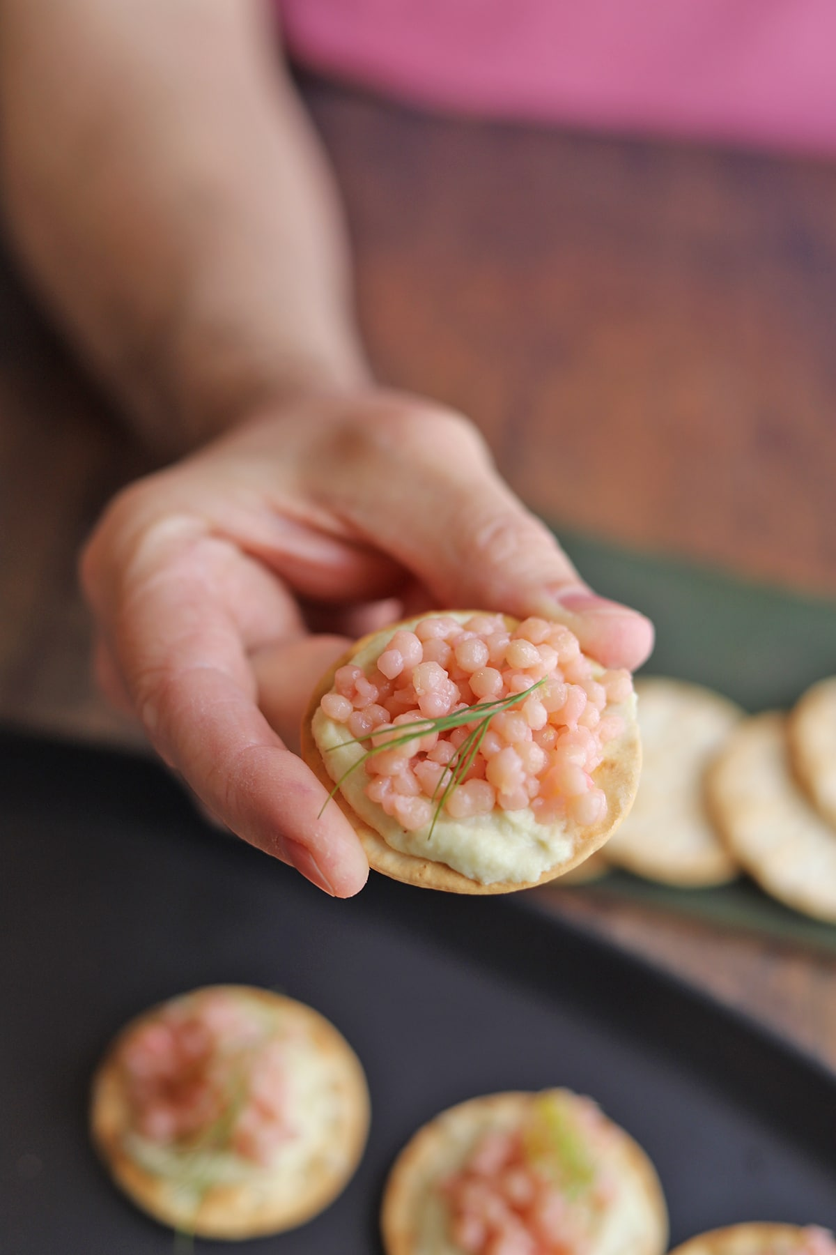 Hand holding cracker with almond cheese, pink couscous, and dill leaf.