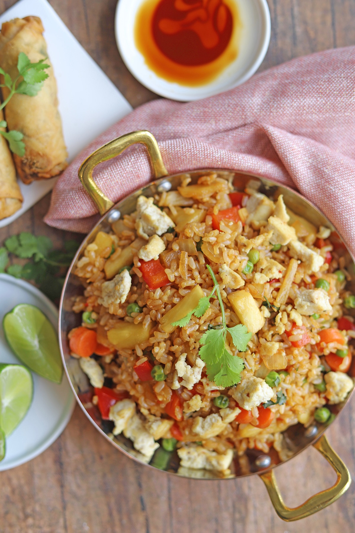 Pineapple fried rice on table with limes, spring rolls, and tamari.