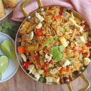 Pineapple fried rice in skillet, topped with eggy tofu.