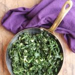 Text overlay: Sauteed kale with garlic. Cooked kale in pan by purple napkin.