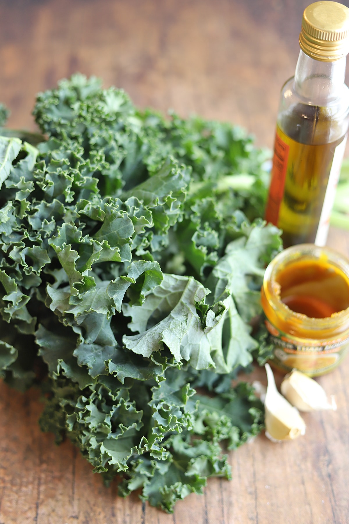 Curly kale on table with garlic cloves, olive oil, and Better Than Bouillon.