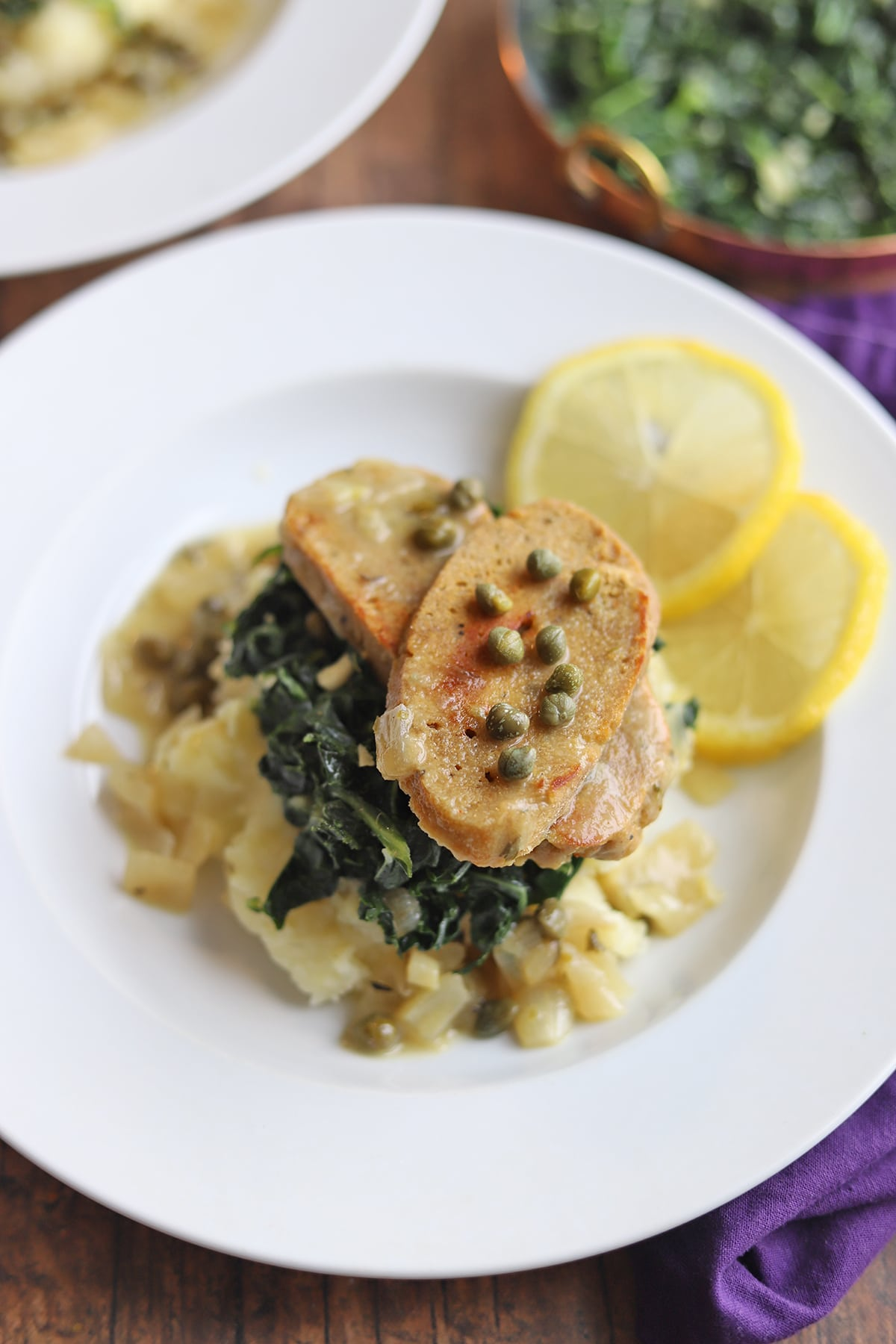 Mashed potatoes on plate, topped with seitan piccata, and sauteed kale.